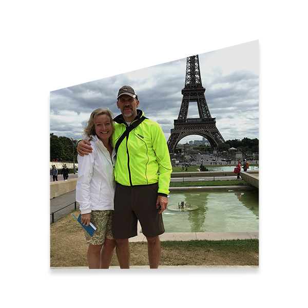 couple standing in front of the Eiffel Tower in Paris