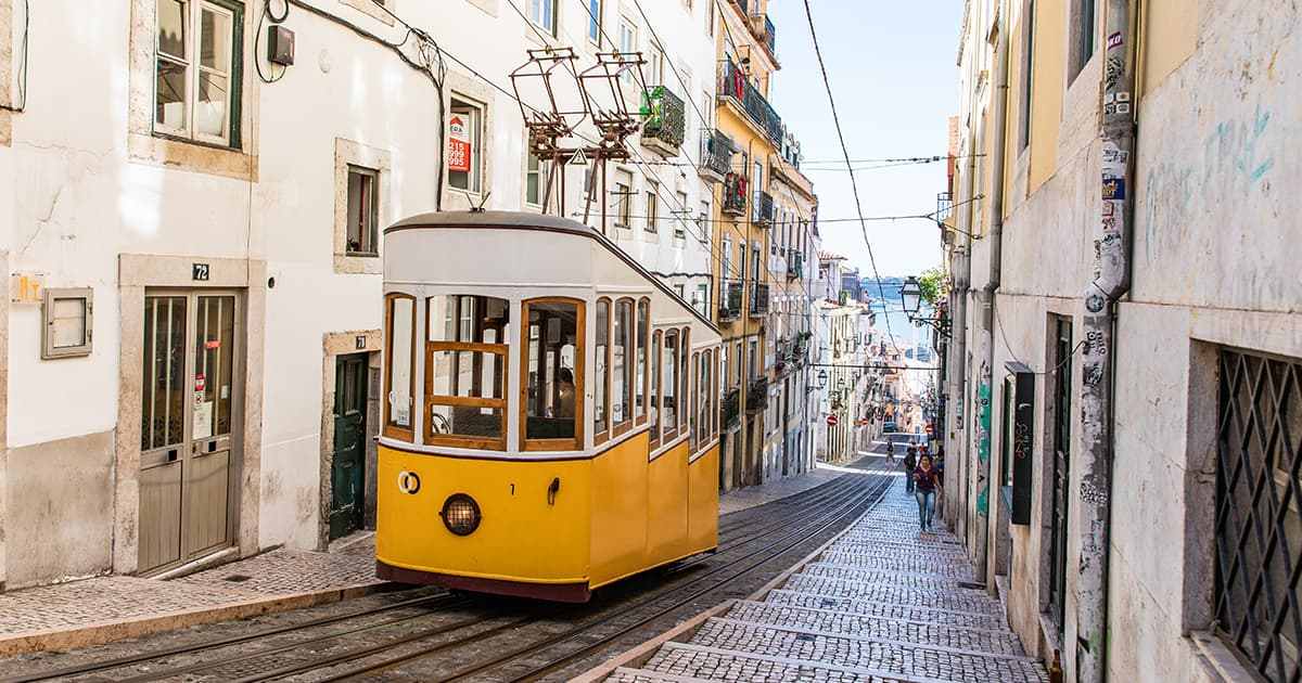 Yellow tram heading uphill on a narrow cobbled street in Lisbon, Portugal